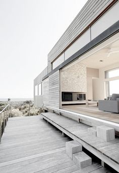 Modern ash wood siding beach house with big windows and an open layout for lots of light.