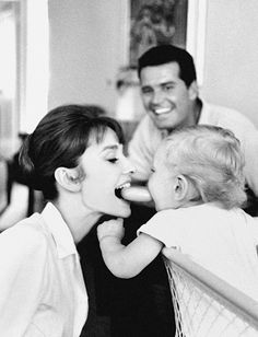 Hepburn playing with her son, Sean Ferrer, while actor James Garner looks on.
