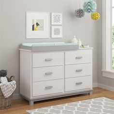 If you're anticipating a little one, this delightful dresser and changing table is the perfect piece to start your nesting. Made in the USA, this piece is crafted of manufactured wood and is founded upon a four leg base finished in a dark brown tone. The rest of the design features a laminated off white finish to keep it versatile, while sleek bar pulls add a dash of metallic style. Keep it in your little one's nursery so you can get started on storage and define your style. Open up i...