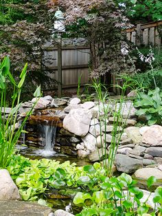 A small patio with Adirondack chairs overlooks this riverbed water feature, which is lined with stone trucked in from the nearby Salmon River.