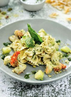Bereiden:Kook de pasta beetgaar in een grote pot gezouten water met een scheutje olijfolie. Pel de scampi's en verwijder het darmkanaal. Kruid met peper en zout en bak krokant op een hoog vuur in een scheutje olijfolie. Doe de courgetteblokjes erbij, bak goudbruin maar zorg ervoor dat de courgette krokant blijft. Draai het vuur lager en overgiet met enkele eetlepels kookvocht van de pasta. Stamp de amandelen en pistachenoten halffijn in de vijzel met 3 flinke eetlepels olijfolie. Schep ...