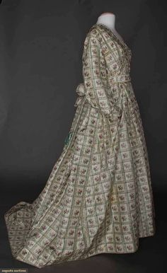 """Maternity dress. 1-piece printed cream silk taffeta in windowpane pattern w/ chine rosebud centers, ruched self fabric trim, entirely lined in cream cotton, CB skirt cartridge pleated, B 38"""", W 34"""", L 57-75"""", includes 1 boned evening bodice & waistband, (originally 2-piece dress, skirt pleats let out in front, bodice attached to skirt for maternity wear, underarm & skirt stains) fair. Sargeant Family, Boston, MA."""