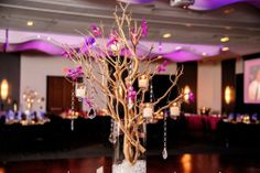 A tall centerpiece design featuring light manzanita branches, purple orchids, crystals and hanging candles  - Design by Leigh Florist - http://www.leighflorist.com