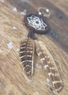 """This stunning 2"""" dream catcher keychain is handmade with leather lace, two beautiful feathers hanging down and has a little nugget of vibrant turquoise woven in. This is the perfect accessory for the"""