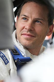 Jacques Joseph Charles Villeneuve, was born (1971) in Saint-Jean-sur-Richelieu, Quebec.  He is a Canadian musician and retired automobile racing driver. He is the son of Formula One driver Gilles Villeneuve. Jacques Villeneuve won the 1995 CART Championship, the 1995 Indianapolis 500 and the 1997 Formula One World Championship, making him only the 3rd driver after Mario Andretti & Emerson Fittipaldi to achieve this. To date, no other Canadian has won the Indianapolis 500 or F1 Drivers'…