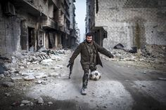 "A Syrian rebel plays football in the Saif al-Dawlah neighborhood of Aleppo, Syria, Wednesday, Jan. 2, 2013. The United Nations estimated Wednesday that more than 60,000 people have been killed in Syria's 21-month-old uprising against authoritarian rule, a toll one-third higher than what anti-regime activists had counted. The U.N. human rights chief called the toll ""truly shocking."" (AP Photo/Andoni Lubacki)"