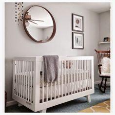White gender neutral nursery with oval mirror