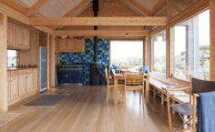 MYE GULVPLASS: Kjøkkenet i denne hytta på Hvaler ligger langs veggene og frigjør på den måten gulvplass. Flisene på endeveggen har en frisk effekt i det trefargede interiøret. Det er et ombygget gjenbrukskjøkken i eik.