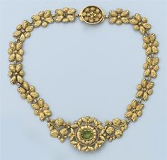 AN ANTIQUE PERIDOT NECKLACE  Composed of gold links chased with flowers, centering an oval peridot to an oval clasp, Dutch, 1815