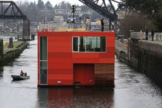 A floating home by E. Cobb Architects makes its way through the Ballard Locks | The Seattle Times