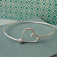 This sweet bracelet is made from a single piece of heavy gauge sterling silver wire that has been lovingly bent and hammered into a stylized heart. Closure unhooks to allow your wrist to slip through. Bracelet measures 7 1/4 inches around.