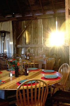 Handmade wood tables, and a hodge-podge eclectic assortment of wooden chairs. Also stacks of old books and oil lamps.