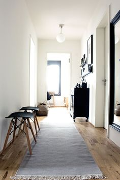 INDECORATE Make-over: modern new building. corridor in Scandinavian style with grey carpet and Eames inspired stools in black