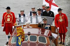 Queen Elizabeth and Prince Philip wave from a boat during a pageant in celebration of the Queen's Diamond Jubilee along the River Thames in central London on June 3, 2012.