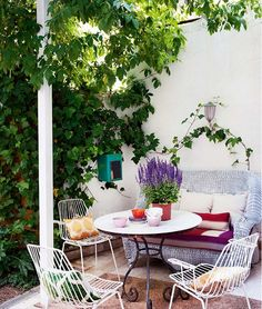 Outdoor dining space with all white metal chairs, a white wicker bench, rod iron table, and beautiful ivy covered walls.
