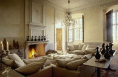plaster walls, crystal chand, limestone fireplace, art on floor, new linen upholstery, awesome coffee table = perfection