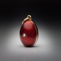 A Vintage Guilloche Enamel Egg Pendant made in Odessa between 1908 and 1917. The front is centered with a tiny rose cut diamond. Height without suspension ring 18 mm (11/16 in.).
