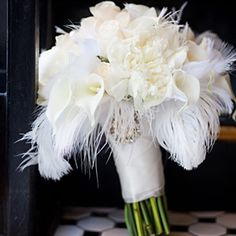 To enhance the glitzy, Gatsby-esque vibe, Corey incorporated feathers into her bouquet and centerpieces.