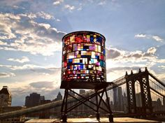 Watertower, a new sculptural artwork by Brooklyn artist Tom Fruin. For the US premiere of his internationally recognized Icon series, Fruin has created a monumental water tower sculpture in colorful salvaged plexiglas and steel. Watertower is mounted high upon a water tower platform becoming part of the DUMBO, Brooklyn skyline.