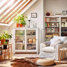 Priestranné a pohodlné biele kreslo FÄRLÖV a skrinka so sklenenými dvierkami HEMNES v bielej miestnosti so šikmým skleneným stropom.