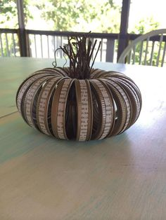 These cute pumpkins are full of charm. They are made from mason jar lid rings and pieces of vine or cinnamon sticks, and adorned with book page