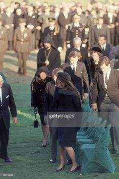 After the funeral of US President John F. Kennedy, former First Lady Jacqueline Kennedy (1929 - 1994) and, among othes, her brothers-in-law Robert F. Kennedy (1925 - 1968) (obscured behind her) and Ted Kennedy (1932 - 2009) (at right) stand to leave the gravesite, Arlington National Cemetery, Virginia, November 25, 1963.