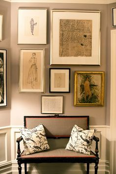 grey walls and fabric bench- but the genius is adding that orange trim and the mix of the art. The pillows are a perfect choice, adding that tracery of black and creamy white - Kate Spade foyer