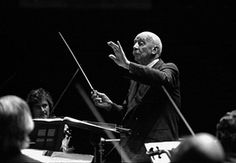 """Sir Adrian Boult, photographed at the Royal Albert Hall on 6 October 1976.  """"I just adore this photo which seems to connect one with a bygone age of gentleman musicians. The elegant suit for a normal rehearsal, the poise, the billiard cue baton. I feel so lucky to have just caught the tail end of the inter-war generation of musicians of whom Sir Adrian was such a magnificent specimen."""" © CLIVE BARDA/ArenaPAL. Photograph: Clive Barda/PR."""