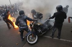 Policemen hold a motorcycle as one of their colleagues catches fire after being hit by a Molotov cocktail during a protest to mark the eight-month anniversary of the Ayotzinapa students' disappearance in Mexico City, May 26, 2015. The students' disappearance on the night of September 26, 2014 in the southwestern city of Iguala triggered massive protests in Mexico and calls for justice. Officials say they were abducted by corrupt...