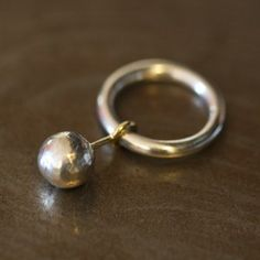 Laurence Oppermann - 'Graine du bonheur' - la petite boule en argent martelé contient une petite pépite, elle est mobile, fixée sur une tige en or 18k - l'anneau est en argent massif - 480€