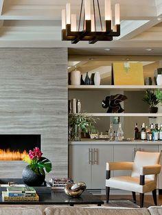 Gray stone fireplace. Mirrored shelf backs. Modern living room.