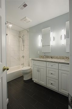 This light and bright bathroom features a double sink vanity with white wooden cabinets and a neutral granite countertop. Black tiles offer a stylish contrast to the gray walls, while Carrera marble tiles line the shower walls. Fluorescent lights are positioned on either side of the mirrors above the vanity.