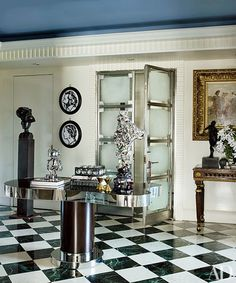 The entrance hall contains a Valdés sculpture on a pedestal (at left), silhouettes by Julian Opie and a Guy de Rougemont table that hosts a KAWS robot | archdigest.com