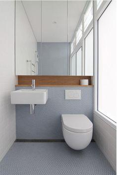 Simple et aéré, combinaison de céramiques et bois, petite étagère intégré, toilette accrochée au mur.