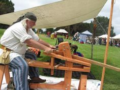 Guy making a hickory bow on his bowyer's bench, which he also made.