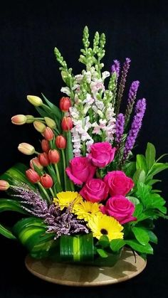 Floral arrangement with gerbera daisies, liatris, snapdragons, tulips, and Heather.