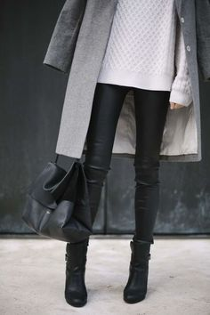 Long manteau gris sobre, pantalon cuir, sac noir ample.