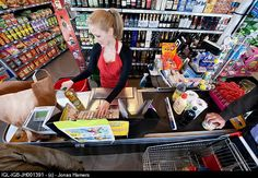 A cashier scans goods and food with clients in a supermarket. (Jonas Hamers)