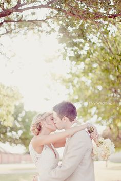 Sunset kiss under the canopy of trees.