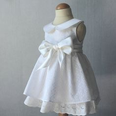 Beautiful christening dress for little girl in broderie anglaise and silk. Decorated with a Peter Pan collar and a large bow at the waist.  * * *
