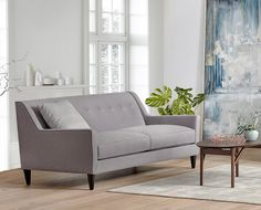 $799 Scandinavian Designs - The Klara sofa is a mid-century beauty fashioned with a tight back and subtle button tufting. The streamlined two-cushion design makes for a modern look, especially when paired with the multiple accent pillows and tapered wood legs.