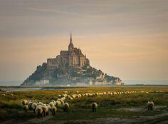 """O Monte Saint-Michel é um ilhote rochoso na foz do Rio Couesnon, no departamento da Mancha, na França, onde foi construído uma abadia e santuário em homenagem ao arcanjo São Miguel. Seu antigo nome é """"Monte Saint-Michel em perigo do mar""""."""