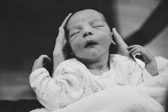 A lifestyle portrait of a newborn being held during an in home family photo session in Boston, Massachusetts - Gina Brocker Photography