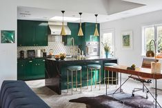 Emerald green cabinets, gold hardware and black marble countertops help create an ultra glam aesthetic in this L.A. kitchen.