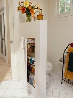 A partial wall is a great way to create a private compartment for the toilet. Put the wall to work by finishing space between the framing with drywall and shelves. A door keeps everything under wraps