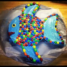 Mac's fish birthday cake!  Two round cake pans, shape second one like fins. Icing. Decorate with M's. Easy!
