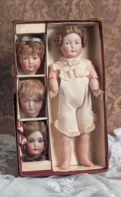 "All original German bisque character doll with three additional heads by J.D. Kestner, circa 1911, marked 182 (head on body) (body is stamped Germany, 183 (smiling), 179 (pouty), and B 171 6 (glass-eyed). Box has original Kestner crown and is marked ""Kestner Character Doll."""