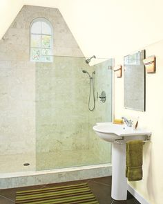 A glass shower enclosures makes this lofty attic bath feel even more spacious.