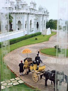 A horse-drawn buggy conveys guests up the drive to the scorpion-shaped Falaknuma Palace (Hyderabad, Andhra Pradesh, India) which was bought by the sixth Nizam of Hyderabad in 1897. Its current tenants, the Taj Group, restored the estate as a luxury hotel that opened in 2010.