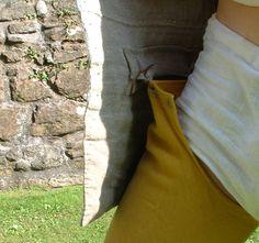 Bösseskytten bär hosor sydda i gult och blått ylle. De är långa och når högt upp på låret och är fästa på insidan av doubleten med snören.